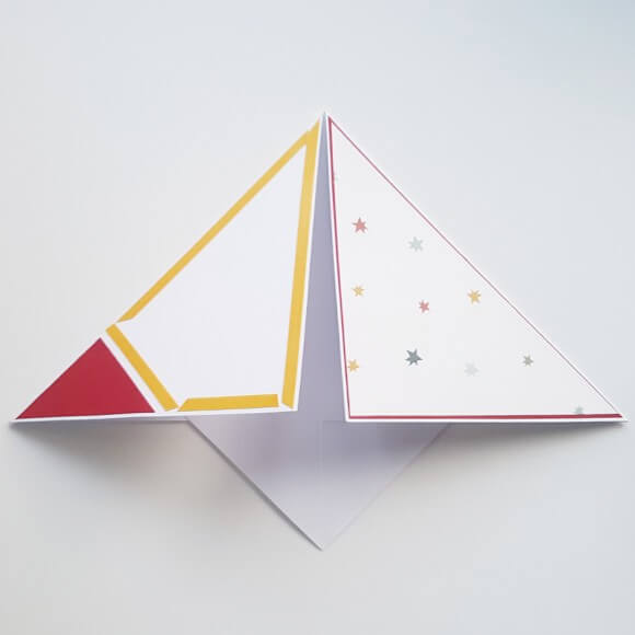 Stick the card together so that you end up with a pyramid shape.