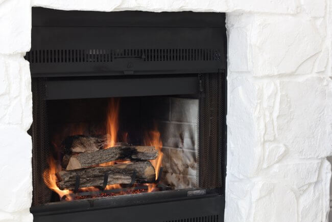 gas fireplace kit installed in fireplace with split oak logs and fire lit